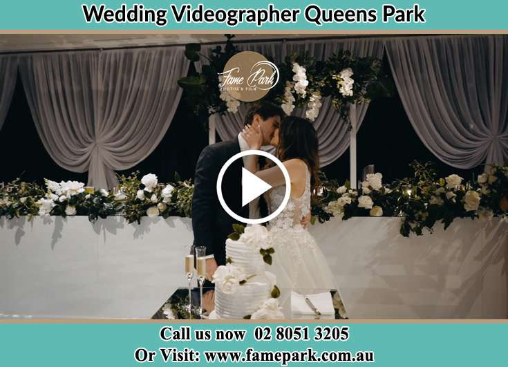 The new couples kissing in front of their wedding cake Queens Park NSW 2022